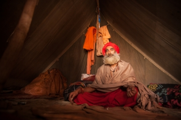 A Hindu holy men inside his tent during the Kumbh mela festival. Haridwar, India. Kumbh Mela is one of the biggest human assemblies on the Earth. The mela (celebration) takes place every 3 years in one of 4 cities in India that are today known as Prayag (Allahabad), Haridwar, Ujjain, and Nasik. Pilgrims spend days travelling from across the country to bath in the river on auspicious dates throughout the festivities.