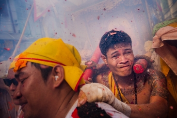 Devotees carrying an idol has a firecracker go off next to his ear as part of the vegetarian festival, Phuket. Thailand.