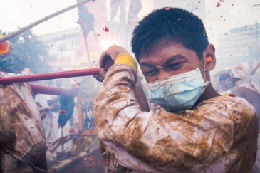 A devotee carrying an idol has a firecracker go off next to his ear as part of the vegetarian festival, Phuket. Thailand.