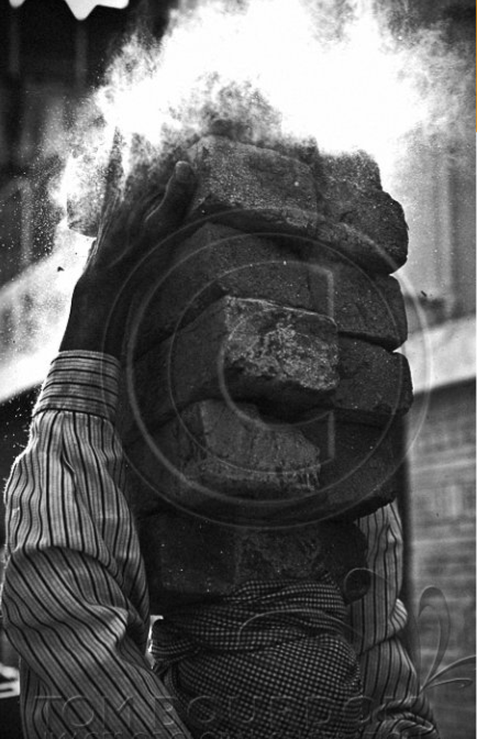 A man carrying bricks on his head. A bad example of using watermarks